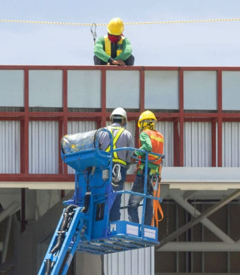 Two Aerial Access engineers demonstrate health and safety on a cherry picker, as determined by the Safecontractor Accreditation.
